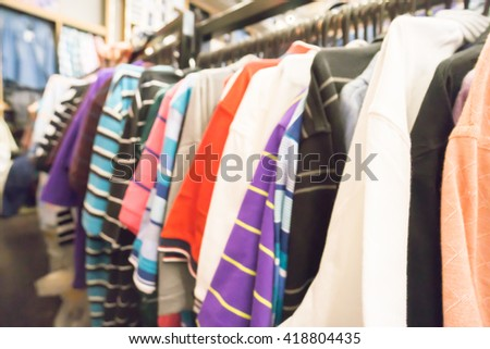 Blurred of Clothes hang on a shelf in store.