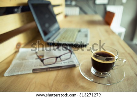 Blurred of cup of coffee with newspaper and notebook - stock photo