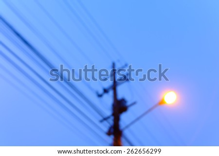 blurred of electricity post with street light. - stock photo