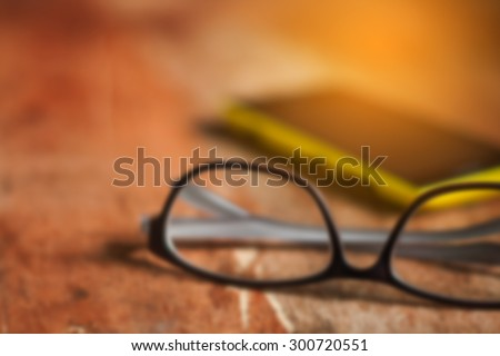 blurred of eyeglasses on wooden table with cellphone,vintage color tone.