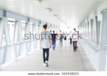 blurred of movement crowd people walking to the airport gate for travel or business:blur of indoor architecture concept:blurry people walking crowded conception.traveler concept.
