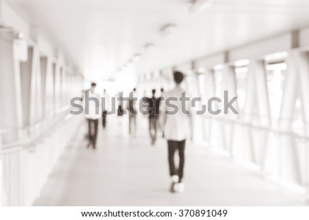 blurred of movement crowd people walking to the airport gate for travel or business:blur of indoor architecture concept:blurry people walking crowded .traveler concept.image with sepia color tone - stock photo