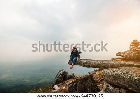 blurred of woman hiking sitting on rock on top mountain at Phu Bakdai, Phu Ruea District, Loei Province, Thailand. subject is blurred and low key