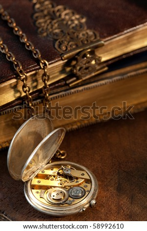 Blurred old books on the background of an antique pocket watch - stock photo