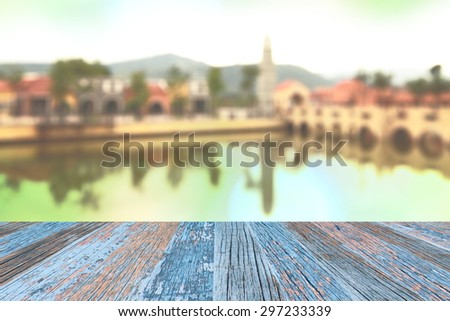 Blurred old fashion city background in the morning pale light with bridge and water in front and mountain in back - stock photo