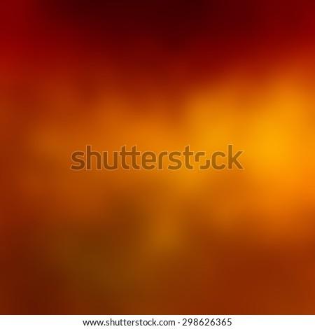 blurred orange autumn background concept, elegant bright orange and red center color splash on black border - stock photo