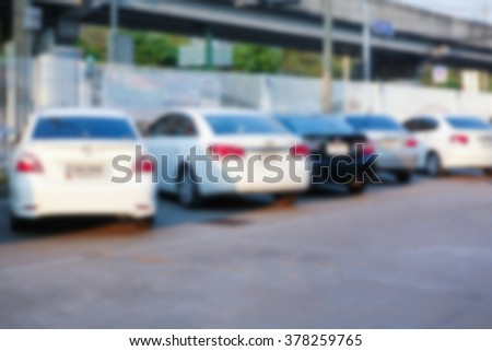 Blurred outdoor cars parking area in public shopping mall. Abstract blur defocused background effect. Background for your business and transportation concept - stock photo