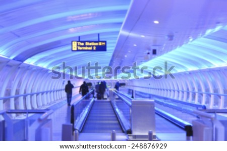 Blurred passenger walking in airport terminal in Manchester - stock photo