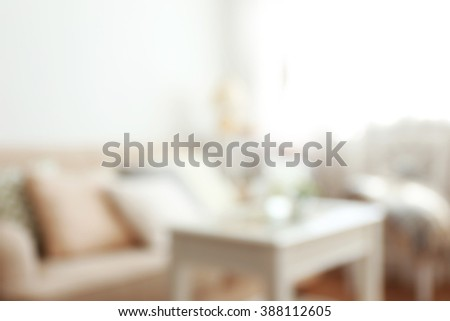 Blurred pastel color sofa with beautiful pillows and vase with flowers on the table in front of it in the room - stock photo