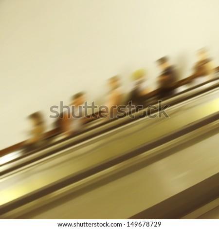 Blurred people on escalator. - stock photo