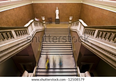 Blurred people on museum staircase.