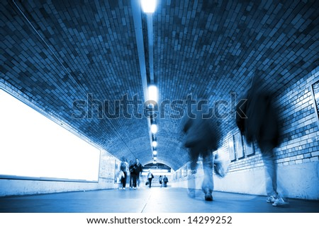 Blurred people on tunnel, blue toned. - stock photo