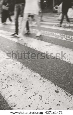 Blurred people on zebra crossing - stock photo
