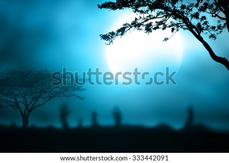 Blurred people raising hands over blur light night background. - stock photo