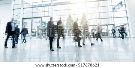 blurred people walking in a modern hall of a Exhibition