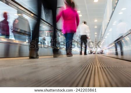 Blurred People Walking on Airport Walkway - stock photo