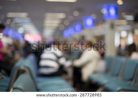 Blurred photo of an airport terminal with unrecognizible passengers passing by with luggage. Blurred background for topics of travel and transportation - stock photo