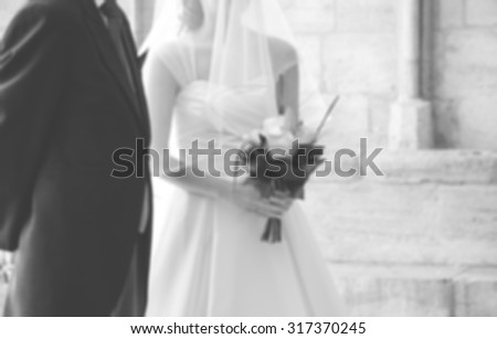 Blurred photo of bride and her father waiting before entering to the Gothic church on wedding day (father is taking his young daughter to the altar). Black and white. - stock photo