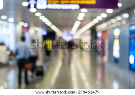 Blurred photo of passengers in airport. Brightly illuminated airports terminal. Travel background - stock photo
