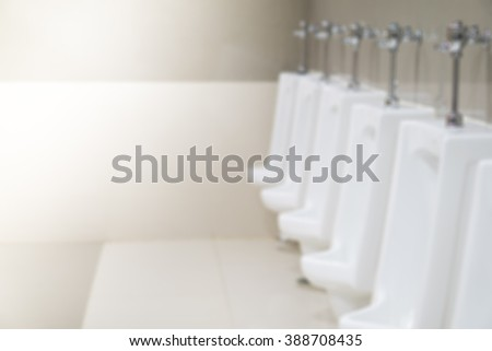 Blurred photo of white urinals in men's public restroom.  - stock photo