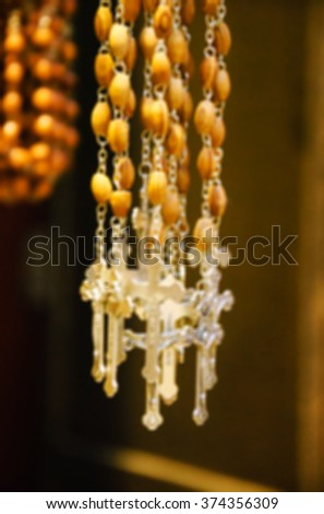 Blurred photo of wooden rosary beads with silver crucifix. - stock photo