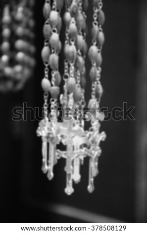 Blurred photo of wooden rosary beads with silver crucifix. Black and white aged photo.