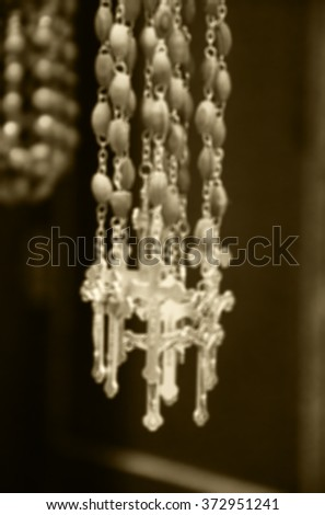 Blurred photo of wooden rosary beads with silver crucifix. Sepia aged photo. - stock photo