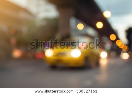 blurred photo of yellow taxi on the road with bokeh background of city street night light. - stock photo