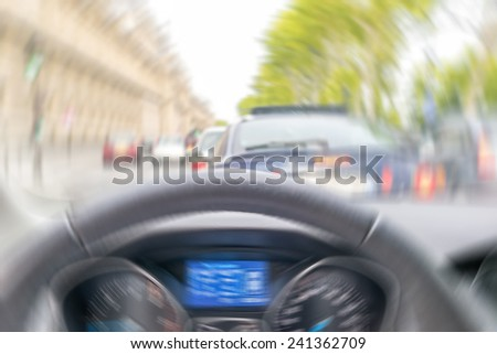 Blurred picture of fast moving car interior in city traffic.