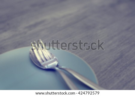 Blurred Picture of Metal Fork and Spoon Setting in Dish on Wooden Table for Background Texture - stock photo