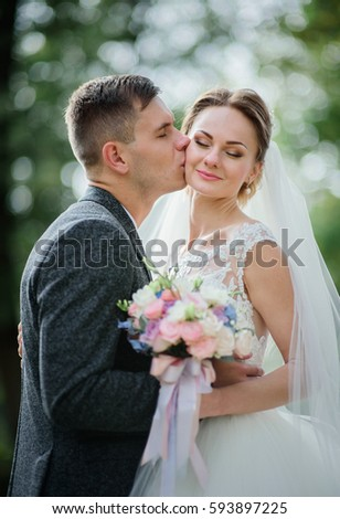 Blurred picture of wedding couple holding colorful wedding bouquet of roses