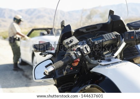 Blurred police officer talking to driver of stopped car on desert highway with focus on motorbike - stock photo