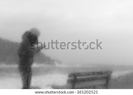 blurred portrait of a woman in a rainy day next to the coast using her smartphone