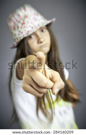 Blurred Portrait of sad girl pointing. Focus on the fingertip. - stock photo