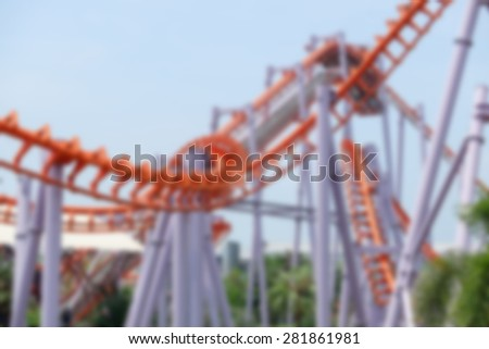 Blurred railroad roller coaster at an amusement park. - stock photo