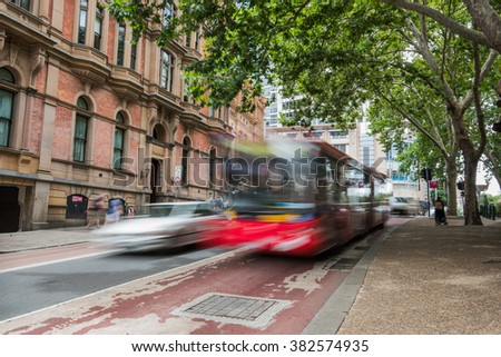 blurred red bus and car on one of the sydney streets during the day - stock photo