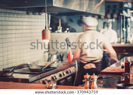 Blurred restaurant interior with salt and pepper on table - stock photo