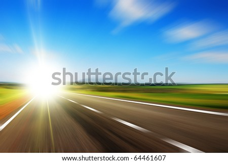 Blurred road and blue blurred sky with a shining sun - stock photo
