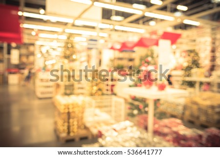 blurred row shelves of plastic christmas bell ornaments garlands lightings and artificial christmas