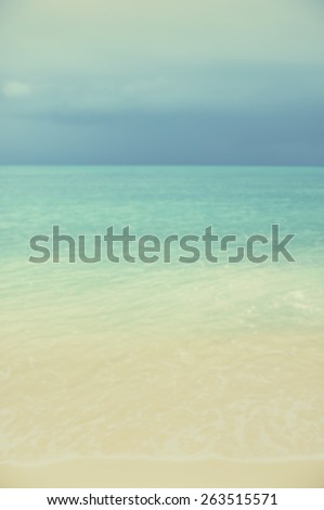 Blurred sea and sand with turquoise seas and dark clouds on the horizon.Designed to work with text overlays including the text colour white. Artistic intent with filters and desaturation.  - stock photo
