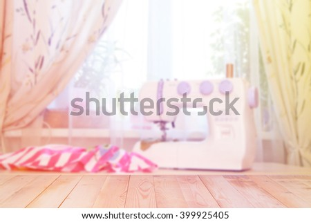 Blurred sewing machine against window with wooden backgroun - stock photo