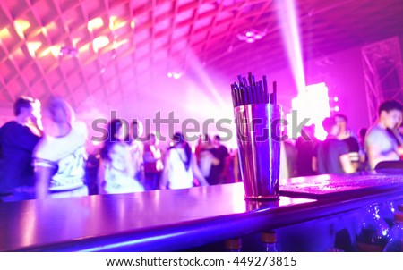Blurred shaker with people dancing - Original pink lights in background - Defocused image for an artistic touch of disco club - Concept of nightlife with music and entertainment