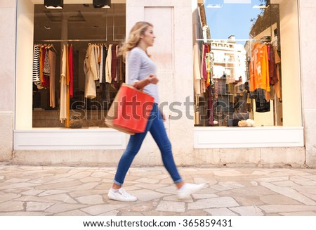 Blurred side figure view of a fashionable young woman walking passed a store shopping window with clothing in a city, outdoors. Consumer lifestyle, tourist visiting and spending, carrying paper bags.