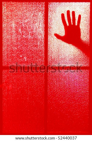 Blurred silhouette of a hand behind a window or glass door, all in the red color (symbolizing horror or fear) - stock photo
