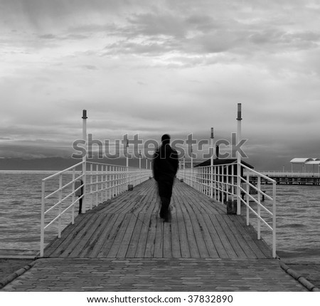 Blurred silhouette of a man on a wooden quay on a lake, black and white - stock photo