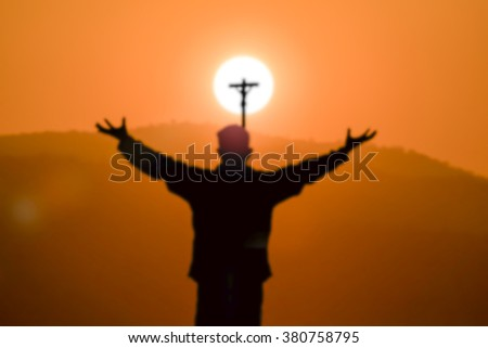 Blurred silhouette of a man praying  cross at mountain on sunset time - stock photo