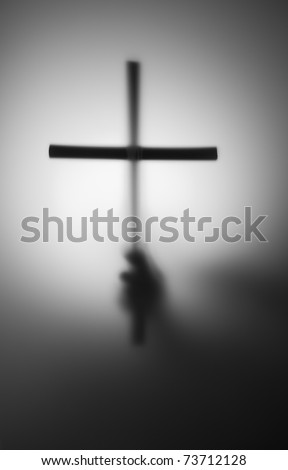 Blurred silhouette of hand with cross in the dark - stock photo