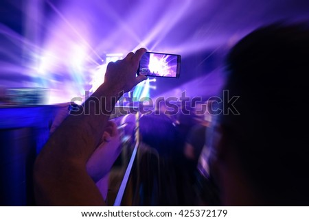 Blurred smart phone screen with defocused background of laser show in modern disco party night club - Defocused image - Concept of nightlife with music - Image with  radial zoom defocusing - stock photo