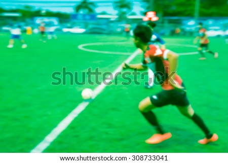 Blurred soccer player in the green field.