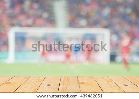 blurred soccer stadium in sunny day backgrounds with old vintage wooden desk tabletop,put and show your products on display or wallpaper - stock photo